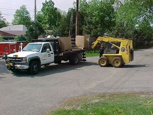 Skid steer unloading boxes from a truck.